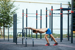 Muscular man warming up before exercise at crossfit ground doing push ups as part of training. Sport concept Stock Photo