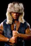 Muscular man warrior with a sword in a fur hat Royalty Free Stock Image