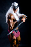 Muscular man warrior with white long hair holding a sword Stock Image