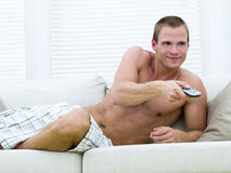 Muscular man watching TV Royalty Free Stock Photo