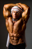Muscular man wearing a Middle Eastern headdress Royalty Free Stock Images