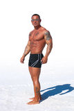 Muscular man on white background with sand Stock Photography