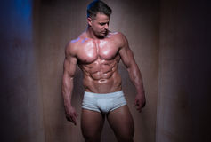 Muscular Man in White Boxer Shorts Looking Down royalty free stock image