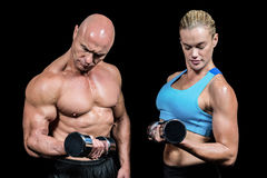 Muscular man and woman concentrating while lifting dumbbells Stock Photo