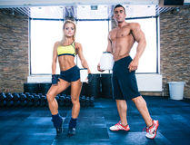 Muscular man and woman holding container with protein. Muscular men and fit women holding plastic container with protein at gym Stock Photography
