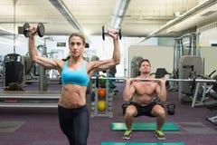 Muscular man and woman lifting weights Stock Photos