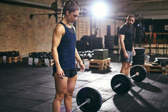 Muscular man and woman standing at barbells Royalty Free Stock Images