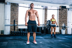 Muscular man and woman workout with barbell Stock Photos