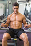 Muscular man working on abdominal machine at the gym Stock Photo