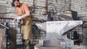 A muscular man working with a circular saw in the forge Stock Photos