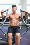 Muscular man working on fitness machine at the gym Royalty Free Stock Image