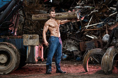 Muscular man. Working on junkyard Stock Image