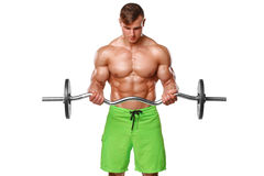 Muscular man working out doing exercises with barbell at biceps, strong male naked torso abs over white background Royalty Free Stock Photography