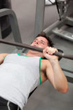 Muscular man working out with dumbbells. In a fitness center Stock Photo