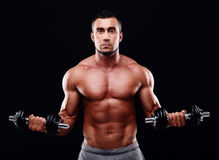 Muscular man working out with dumbbells Royalty Free Stock Images