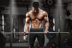 Muscular man working out in gym doing exercises with barbell at biceps, strong male naked torso abs.  Royalty Free Stock Photos