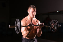 Muscular man working out in gym doing exercises with barbell close-up, strong male naked torso abs. Stock Photos
