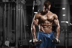 Muscular man working out in gym doing exercises with barbell, strong male naked torso abs Stock Photography