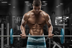 Muscular man working out in gym doing exercises with barbell, strong male naked torso abs royalty free stock images