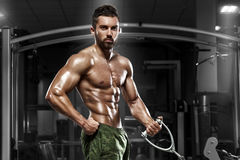 Muscular man working out in gym doing exercises at biceps, strong male naked torso abs.  Royalty Free Stock Images