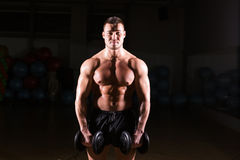 Muscular man working out in gym doing exercises with dumbbells at biceps, strong male naked torso abs. Muscular man working out in gym doing exercises with Royalty Free Stock Images