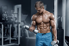 Muscular man working out in gym doing exercises with dumbbells, bodybuilder male naked torso abs.  stock photo