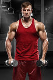 Muscular man working out in gym doing exercises, strong male Stock Image