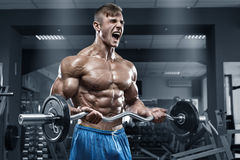 Muscular man working out in gym doing exercises, strong male naked torso abs Stock Photos