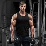 Muscular man working out in gym doing exercises, strong male torso.  Royalty Free Stock Image