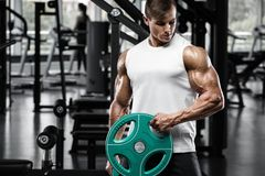 Muscular man working out in gym doing exercisess, strong male bodybuilder stock image