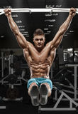 Muscular man working out in gym, doing stomach exercises on a horizontal bar, strong male naked torso abs Stock Photo