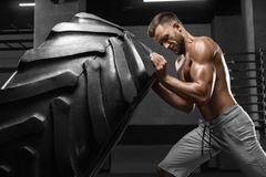 Muscular man working out in gym flipping tire, strong male naked torso stock photos