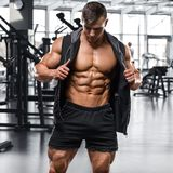 Muscular man working out in gym, strong male naked torso abs royalty free stock images