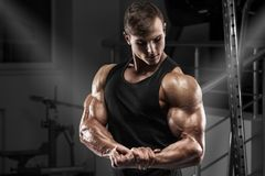Muscular man working out in gym. Strong male showing muscles biceps Royalty Free Stock Images