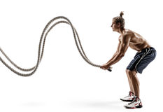 Muscular man working out with heavy ropes. Photo of sporty male with naked torso isolated on white background. Strength and motivation. Side view. Full length Stock Photos