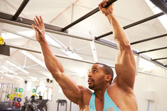 Muscular man working out on monkey bars at a gym Royalty Free Stock Image