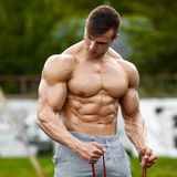 Muscular man working out outdoor, doing exercise. Strong male naked torso abs, outside.  royalty free stock image