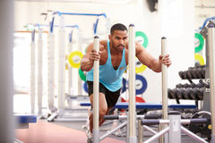 Muscular man working out using equipment at a gym Stock Images