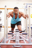 Muscular man working out using equipment at a gym, vertical Stock Photos