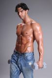 Muscular  Man Workout. Muscular young man shirtless and sweaty in jeans working out lifting weights Royalty Free Stock Photography