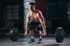 Muscular man workout with barbell at gym. Closeup portrait of a muscular man workout with barbell at gym. cross fit and fitness Stock Images