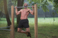 Muscular Man Workout On Bars In Outdoor Gym Stock Photo
