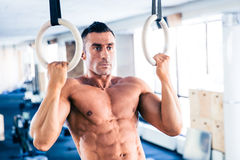 Muscular man workout on fitness ring Stock Photos
