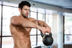 Muscular man workout with kettle ball. Portrait of a muscular man workout with kettle ball in fitness gym Royalty Free Stock Image