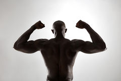 Muscular man& x27;s back in silhouette Royalty Free Stock Photography