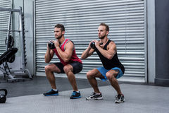 Muscular men exercising with kettlebells Stock Photo