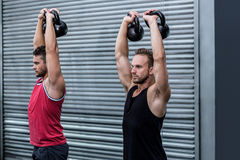 Muscular men lifting a kettle bell Stock Image