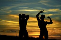 Muscular men in sunset with boxes. Muscular men or bodybuilders silhouettes, handsome, young, male athlete people with sexy torso outdoors in sunset sky Royalty Free Stock Photography