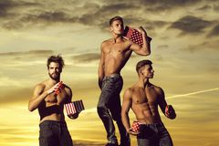 Muscular men in sunset with boxes. Three men or bodybuilders, handsome, young, male athlete people with sexy, muscular torso outdoors in sunset sky. guys holds royalty free stock photography