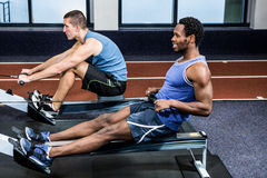 Muscular men using rowing machine Stock Photography